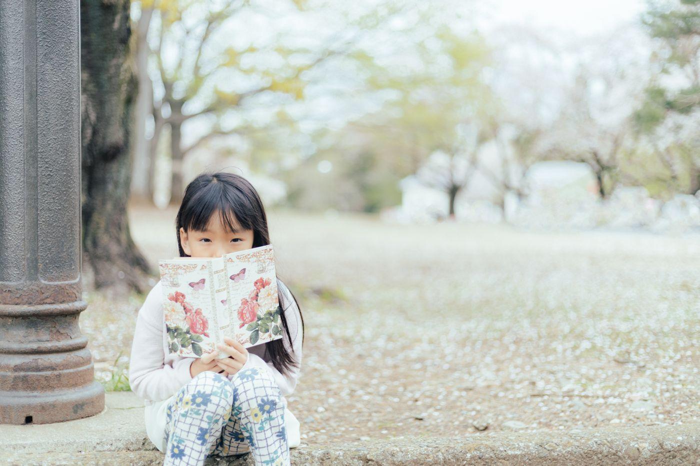 公園で洋書を読む女の子の写真