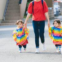 ママと手をつなぐ双子の女児の写真