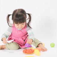 お皿に盛り付けするおままごと女児の写真
