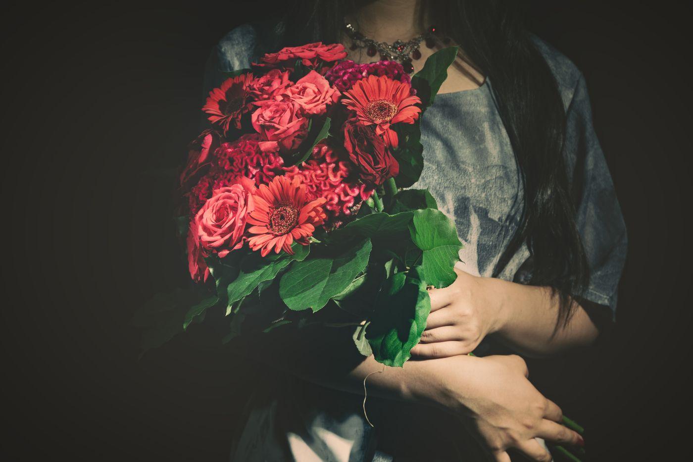 バラの花束をを抱えた女性の写真