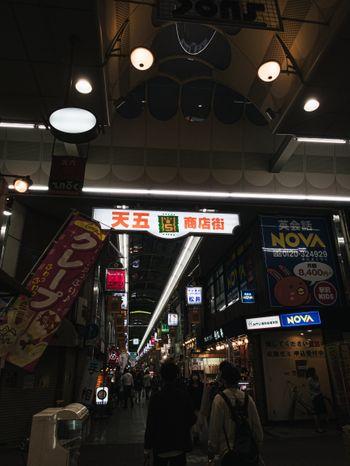 商店街入り口の大きな看板と行き交う人の写真