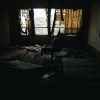 カーテンの隙間から照らされる瓦礫まみれの椅子の写真