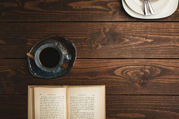 喫茶店のテーブルに置かれた洋書とコーヒーの写真
