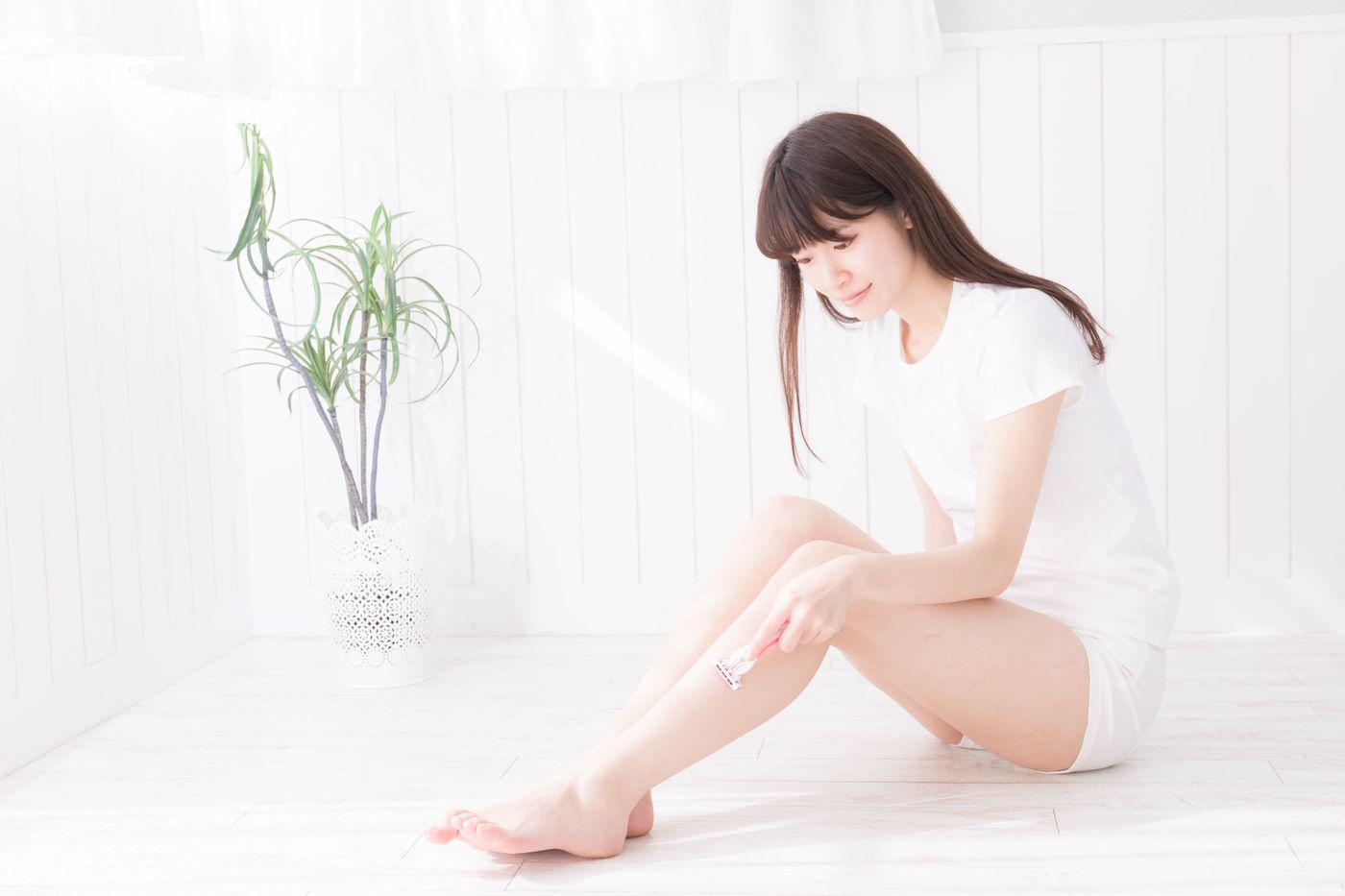 座りながら膝下をT字カミソリで脱毛する女性の写真