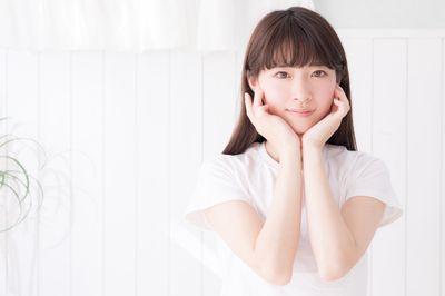 白い壁の前で顎乗せポーズする女性の写真