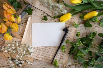 机の上に置かれた花と万年筆の写真