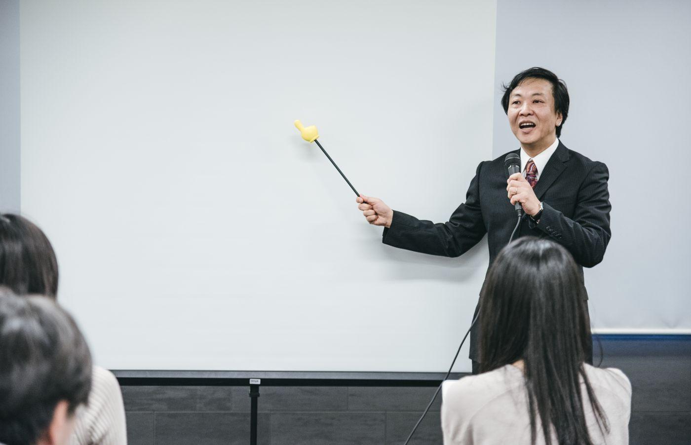 ホワイトボードを見ながら登壇するセミナー講師の写真