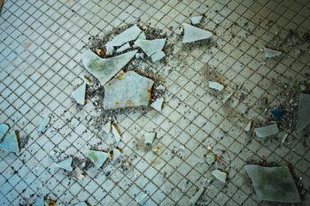汚れたタイルと飛び散るガラス片の写真