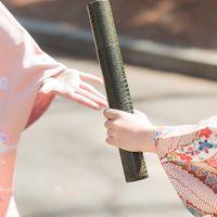 卒業証書の丸筒をリレーのバトンのように手渡す様子の写真