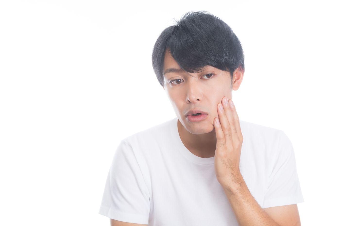頬の肌荒れを気にする男性の写真