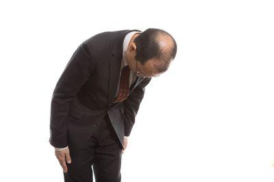 お辞儀で禿げた頭頂部を見せるサラリーマンの写真