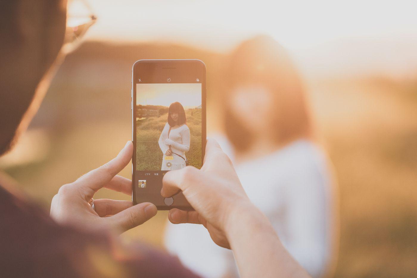 逆光の中、iPhone 8 のポートレートモードでグラドルを撮影中のブロガーの写真