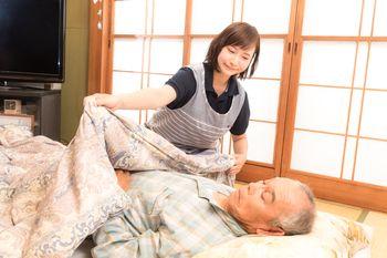 お爺さんに布団をかぶせる介護士の女性の写真