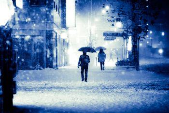 積雪で電車が止まり傘を差して家路に向かうの写真