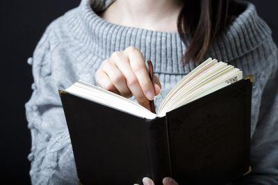本に栞をはさむ女性の写真