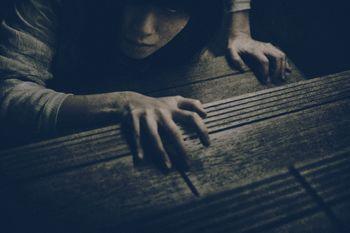 階段に爪を立ててこちらを睨みつける女性の写真