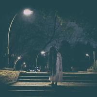 公園のライトの下で佇む髪の長い女性の写真