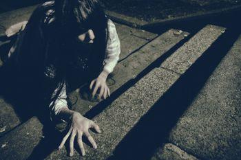 階段を這いながら上りきろうとする女性の写真