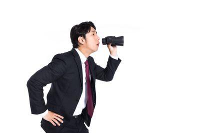 双眼鏡を持ってサボっている従業員を監視するリーダーの写真