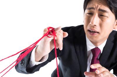 たくさんの運命の赤い糸に困惑する男性の写真