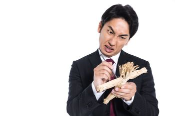 藁人形に五寸釘を刺すサラリーマンの写真