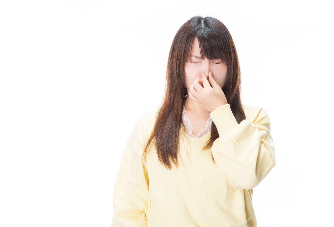 衝撃的なにおいに思わず目を閉じる女性の写真