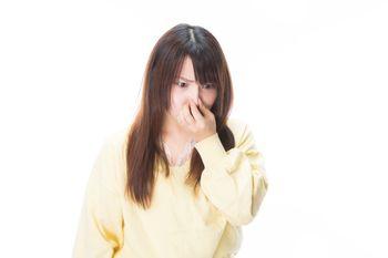 臭いの根源を凝視する女性の写真