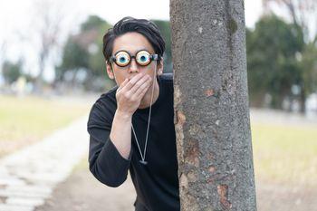 目を丸くして驚く木陰男の写真