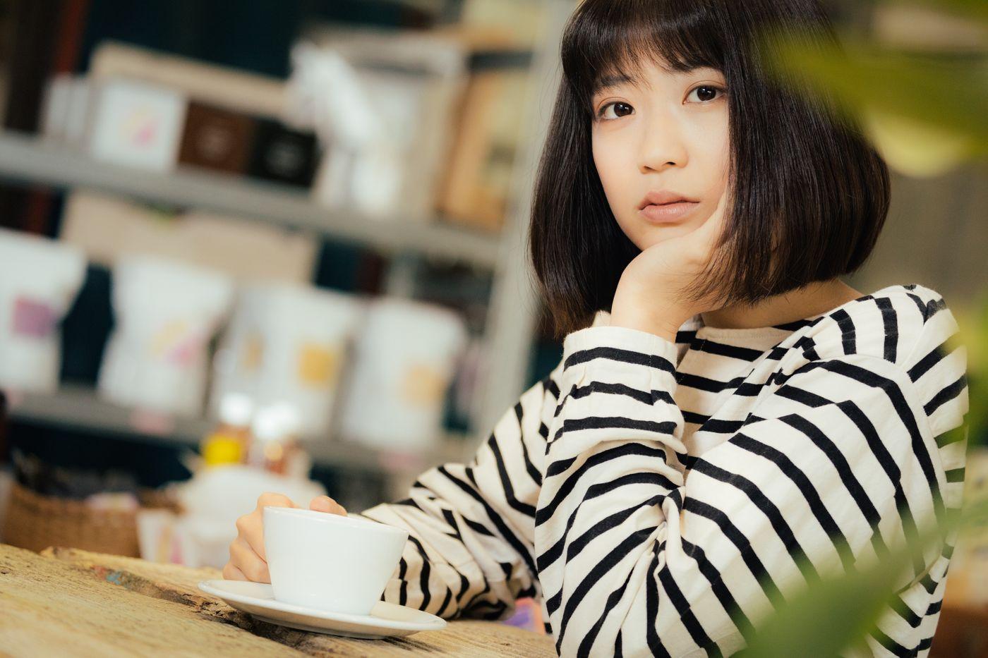 カフェで退屈そうにこちらを見つめる女性の写真
