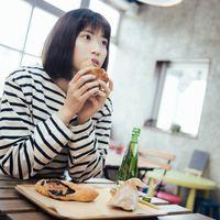 フードコートでおやつに菓子パンを食べる女性の写真