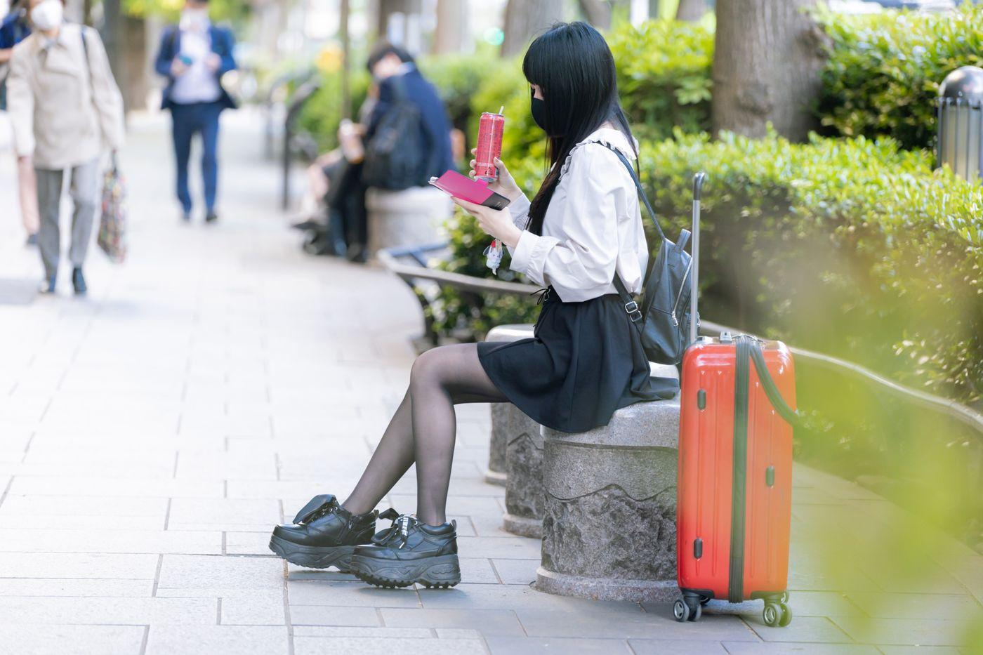 ピンモン片手に待ち合わせをしている女性の様子の写真
