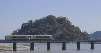 虚空蔵島をバックに走る観光列車「海幸山幸」の写真