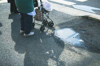 歩道に伸びる手押し車の影の写真