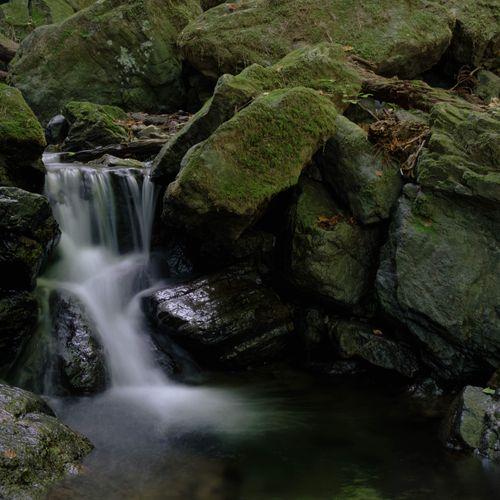 険しい山道の岩場と小さな滝の写真