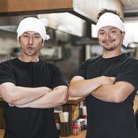 ラーメン屋で働くアルバイトのふたり(ひとりは外国人留学生)の写真