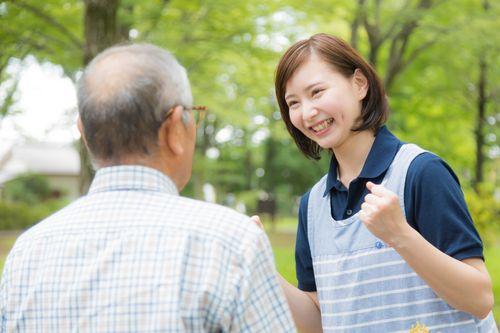 高齢者を元気づける笑顔が素敵な女性介護士の写真