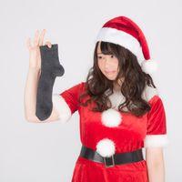 男性用靴下にプレゼント入れるのを嫌がる女性サンタの写真
