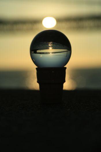 水晶に映る夕日と橋の写真