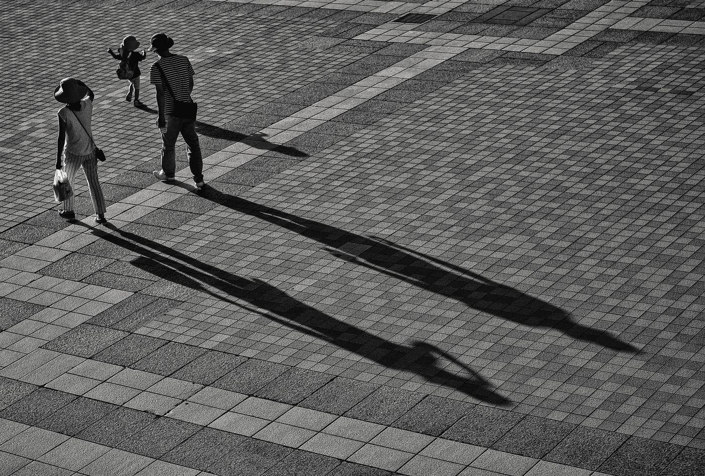 お出かけ中の家族連れと伸びる影の写真
