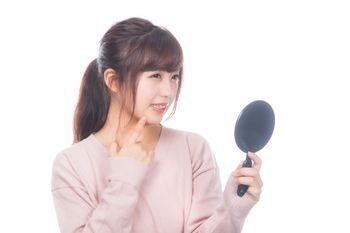 手鏡で吹き出物を見る女性の写真