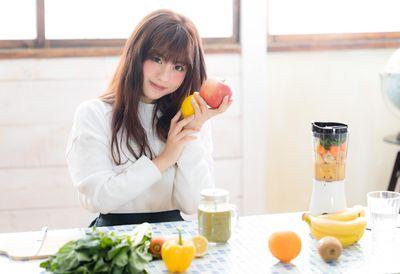 リンゴとレモンを持って微笑むスムージー女子の写真