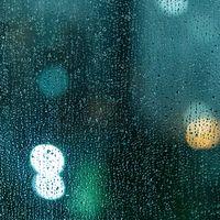 ガラス窓いっぱいの雨粒の写真