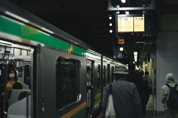 ホームに停まる電車と乗客の写真