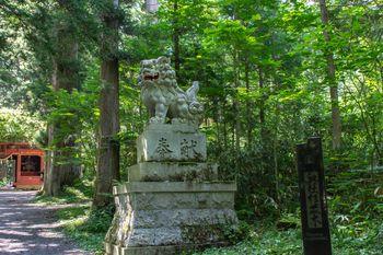 随神門手前で迎えてくれる狛犬と奥社杉並木の碑の写真