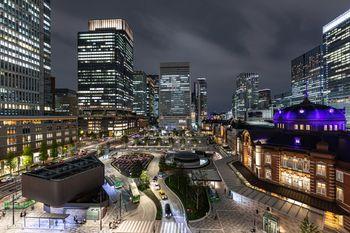 夜の東京駅丸の内駅前広場を取り囲む高層ビル群と駅舎の写真