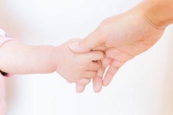 親の手を握る赤ちゃんの手の写真