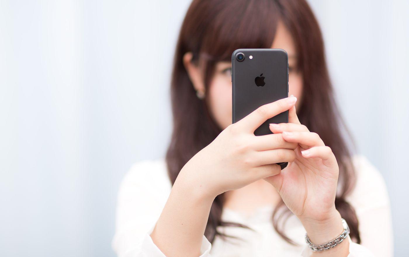 マットブラックカラーのスマートフォンを操作する女性の写真